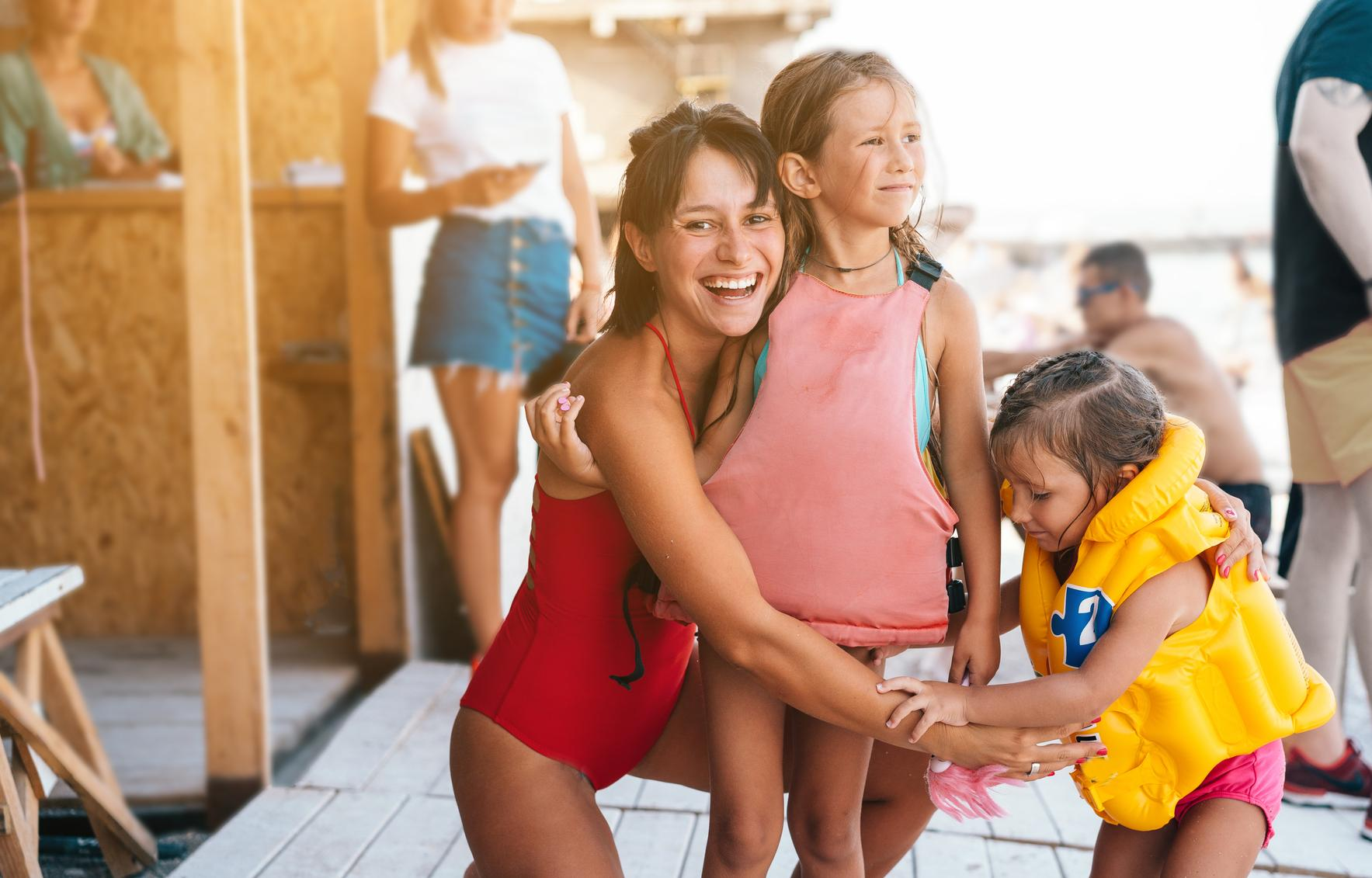 Mother Helps Children Put On Life Jackets For Boat