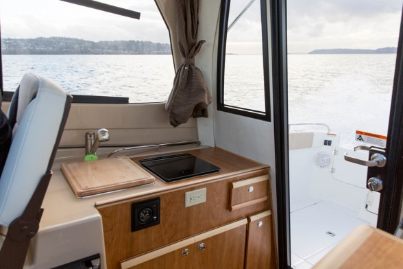 A simple galley with a fresh water mixer and sink on a modern power boat. Cutwater photo.