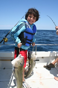 Your kids will bemiserable if you force them to wear bulky, uncomfortable lifejackets. While young David Rudow is happy about his double tilefish hookup here, also note the easy-to-wear lifejacket his dad has fitted him with. Photo byLenny Rudow.