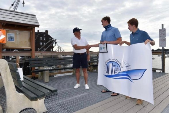 Rob Howie, Commodore of the Corinthian yacht club in Marblehead presenting Brian (left) and Noah (right) with a green-company certificate.