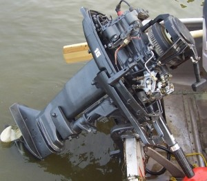 A photo of an outboard hanging off the back of a boat.