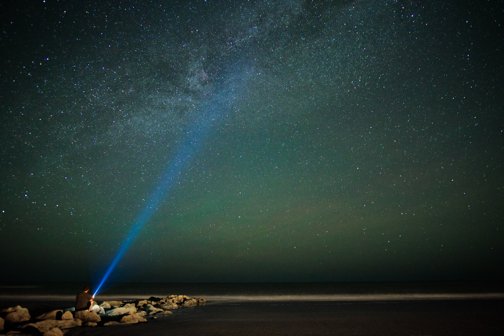 man-with-flashlight-by-the-sea