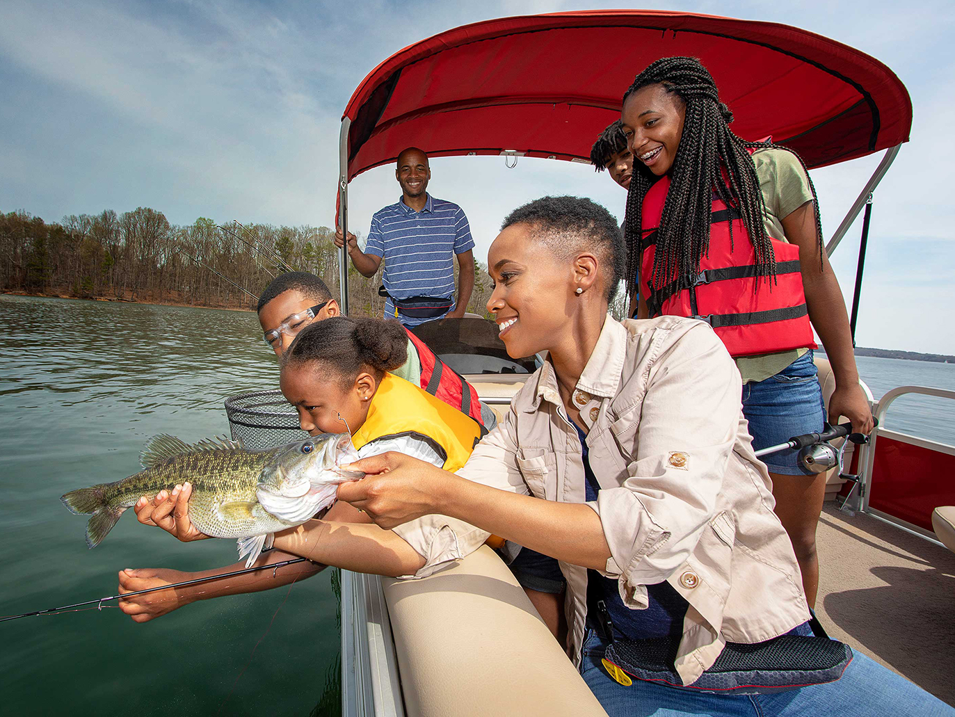 Mother And Father With Children Fishing On A Pontoon Boat