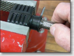 Clamp the tool in a vice and twist the hose assembly into the snout of the Koul Tool.