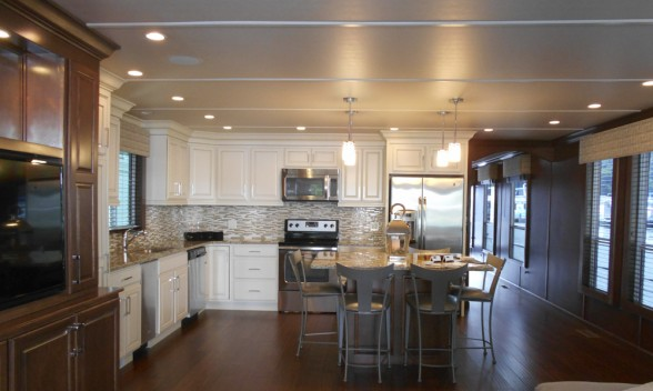 It's hard to believe that this large open floor plan along with this beautiful kitchen stocked with full-size appliances actually lives within the walls of a Thoroughbred Houseboat. Photo credit: Trifecta Houseboats.