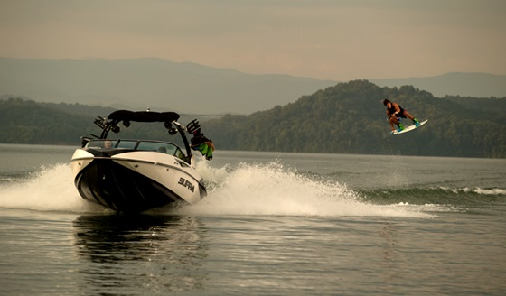 A wakeboarder gets big air behind a purpose-built  Supra tow-boat.