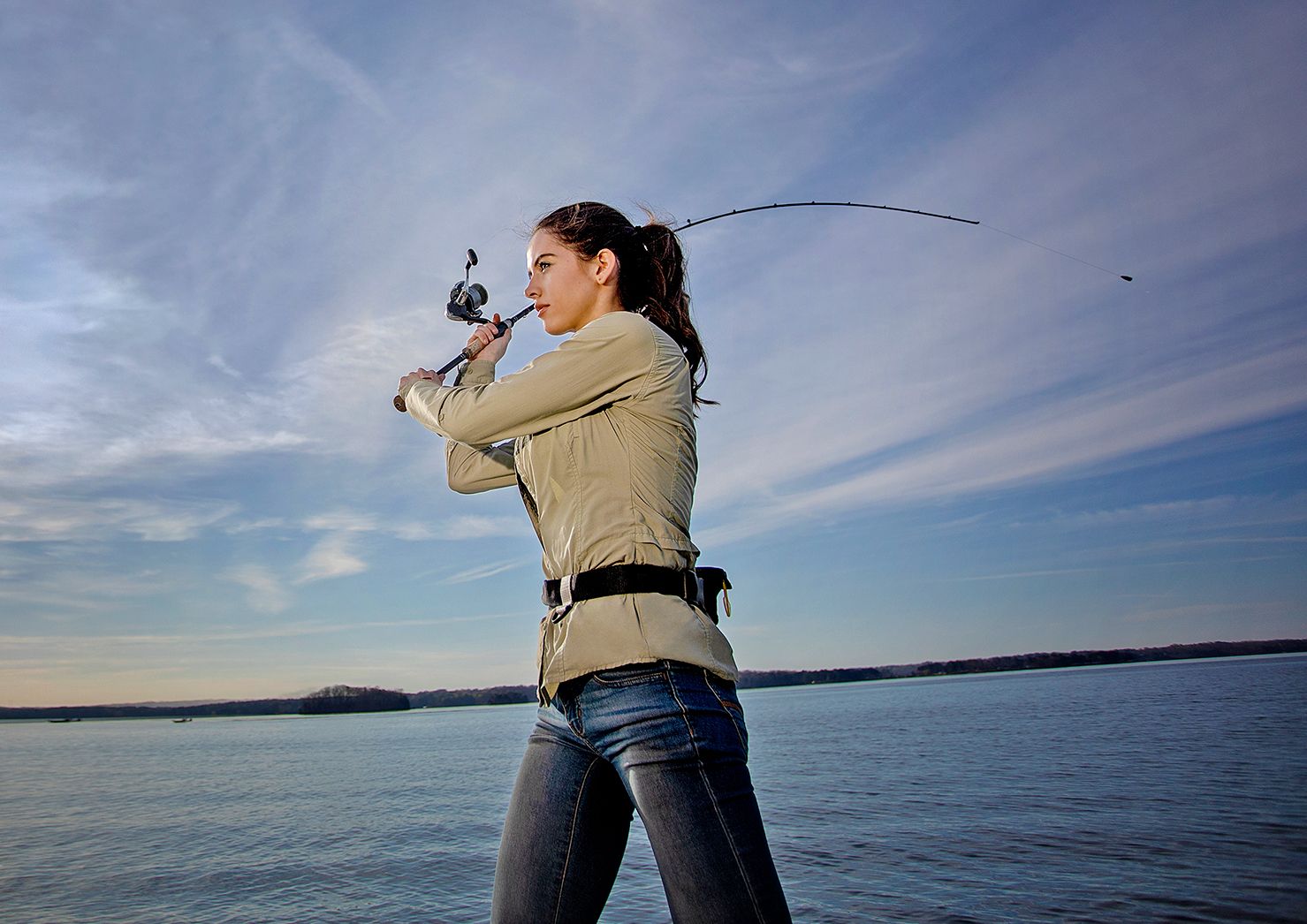 Woman On A Boat Casting A Fishing Rod